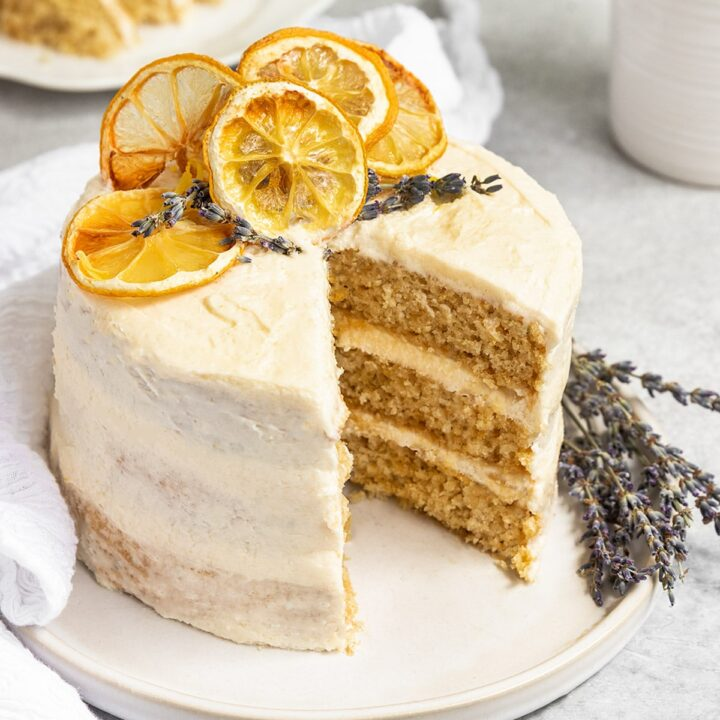 three layer cake with lemon frosting and dried lemons and dried lavender on top