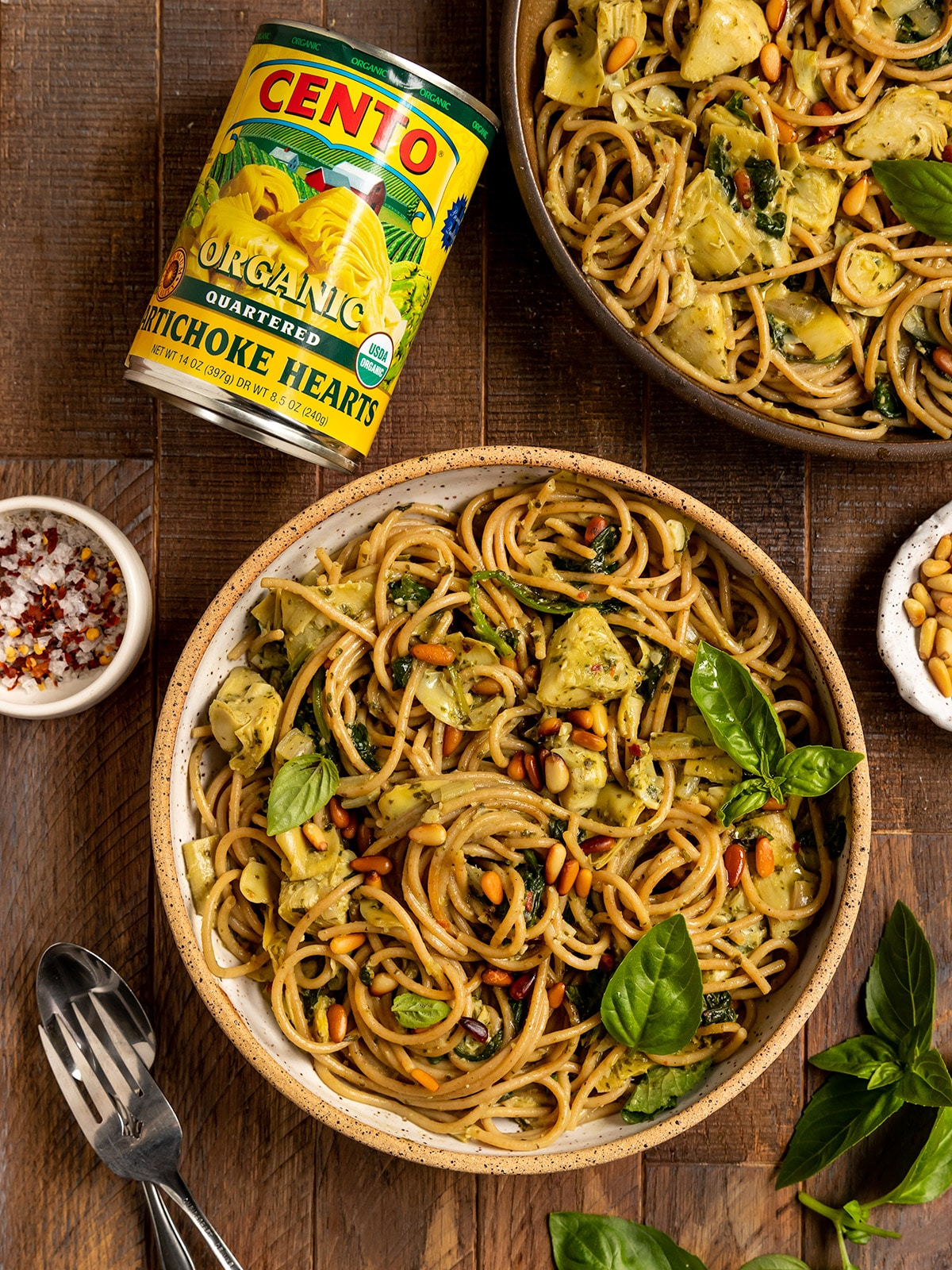 two bowls of linguine with spinach, artichokes, basil, and toasted pine nuts with cento canned artichokes on side