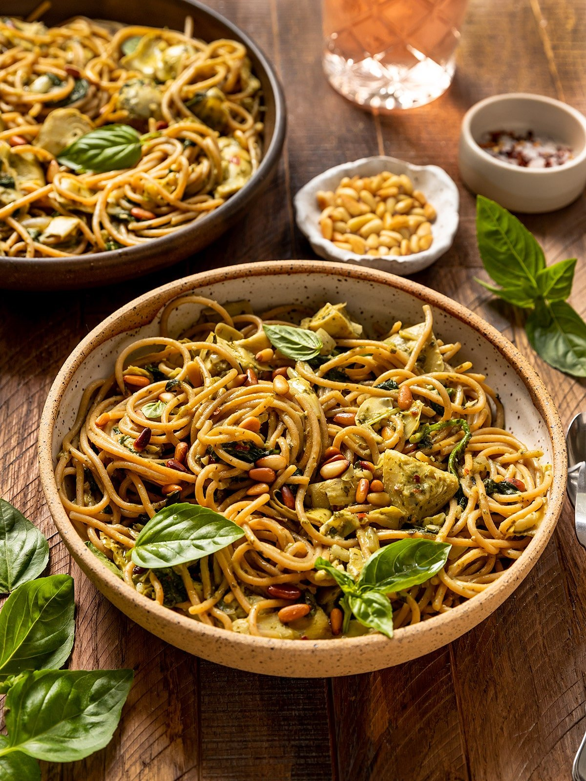 two bowls filled with linguine, basil sauce, artichokes, spinach, and topped with toasted pine nuts and fresh basil