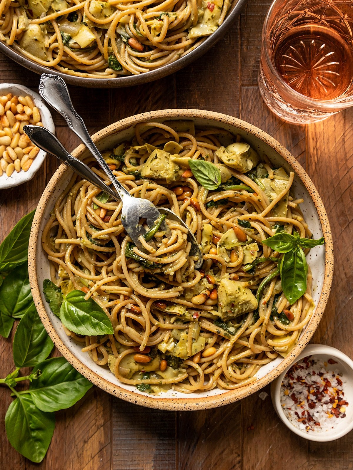 bowl of pasta with spinach artichoke, basil, pine nuts, and two forks swirled in noodles