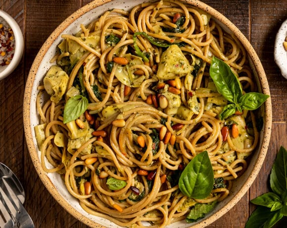 bowl of linguine with spinach, artichokes, basil, and toasted pine nuts