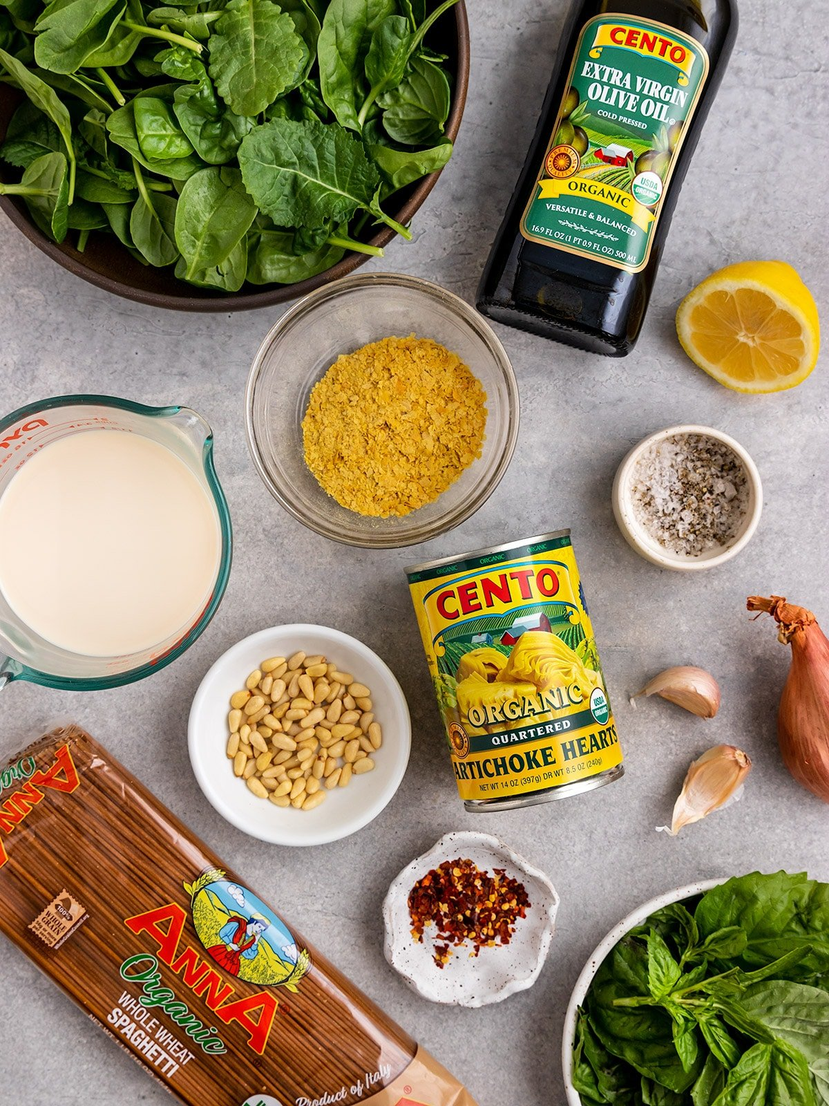 picture of ingredients for spinach artichoke pasta including pasta, artichokes, spinach, basil, salt, pepper, lemon, shallot, garlic, chili flakes, oat milk, and nutritional yeast