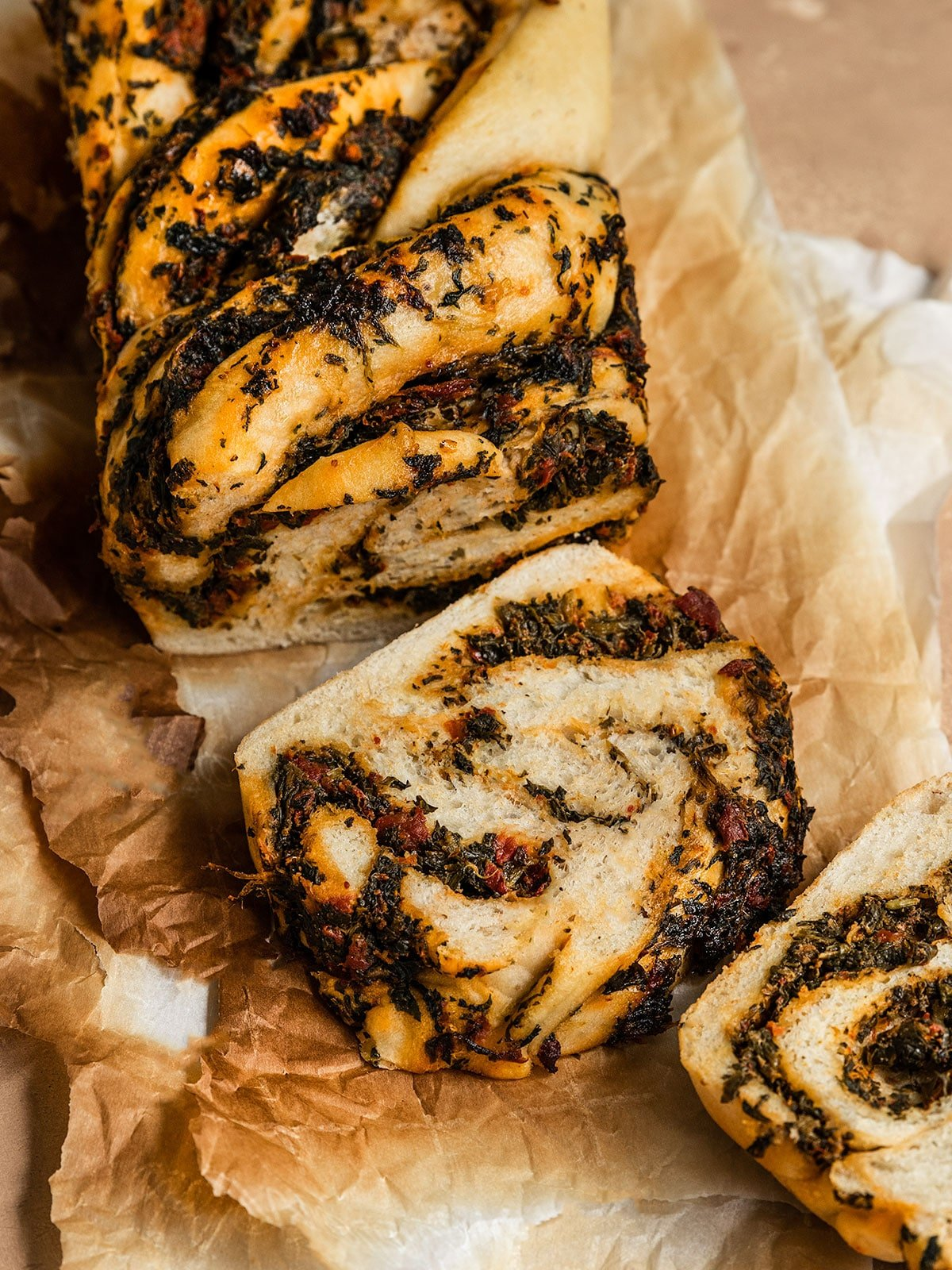 sliced babka with swirls of tomato spinach filling on a sheet of parchment paper