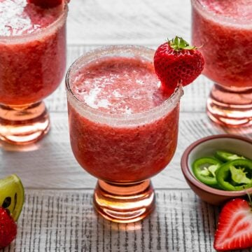 strawberry jalapeno margarita in a glass with lime sugar rim and fresh strawberry on top