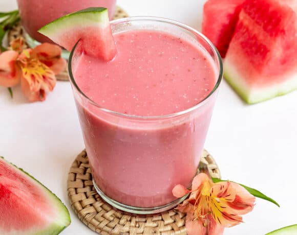two watermelon strawberry smoothies with watermelon wedge on top with slices of fresh watermelon on side