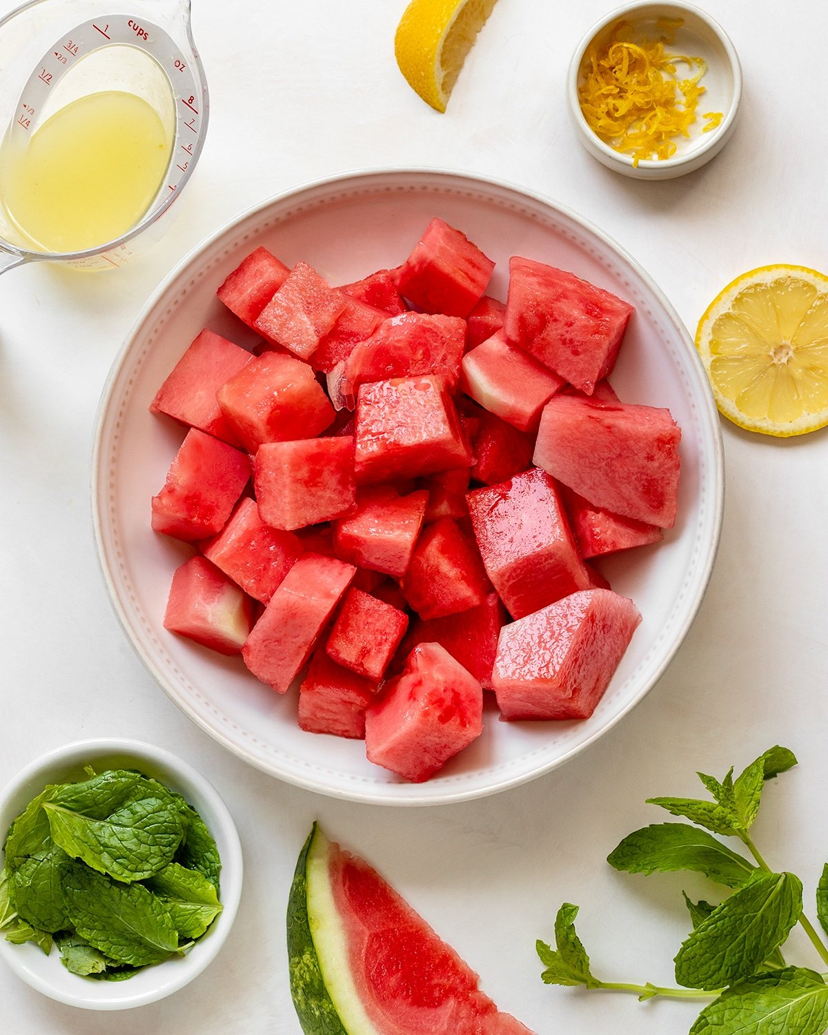 watermelon popsicle ingredients including bowl of seedless watermelon, lemon juice, lemon zest, and fresh mint leaves