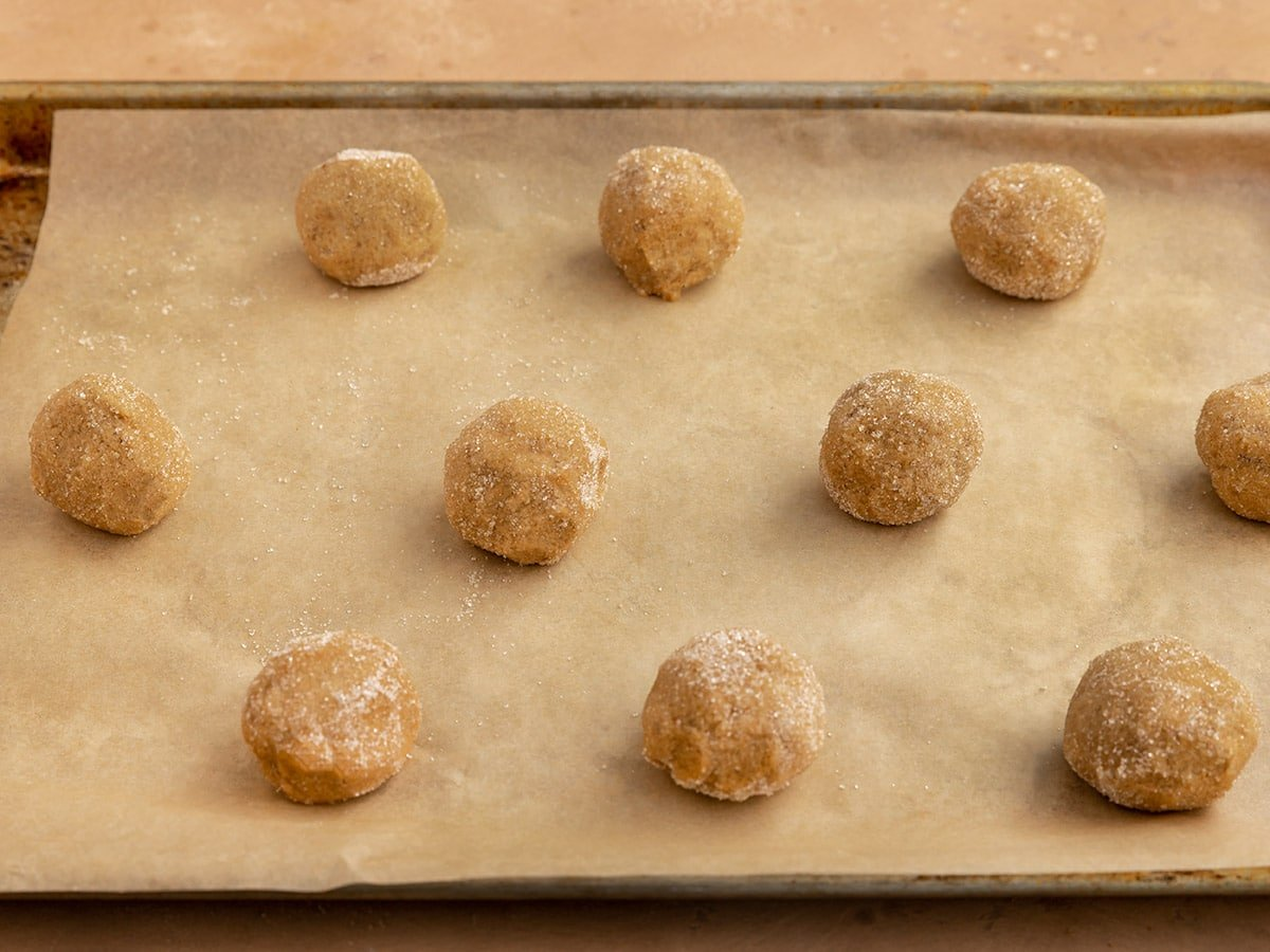 cookie dough balls rolled in sugar on a parchment paper lined baking tray