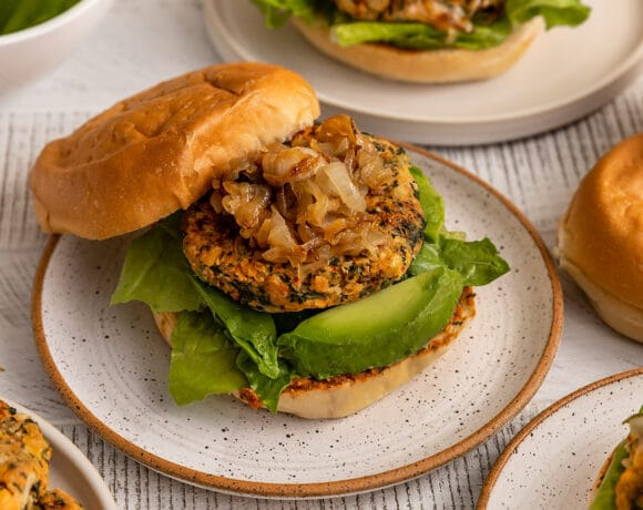 plate filled with burgers that have lettuce, avocado, chickpea spinach burgers, and caramelized onions on top