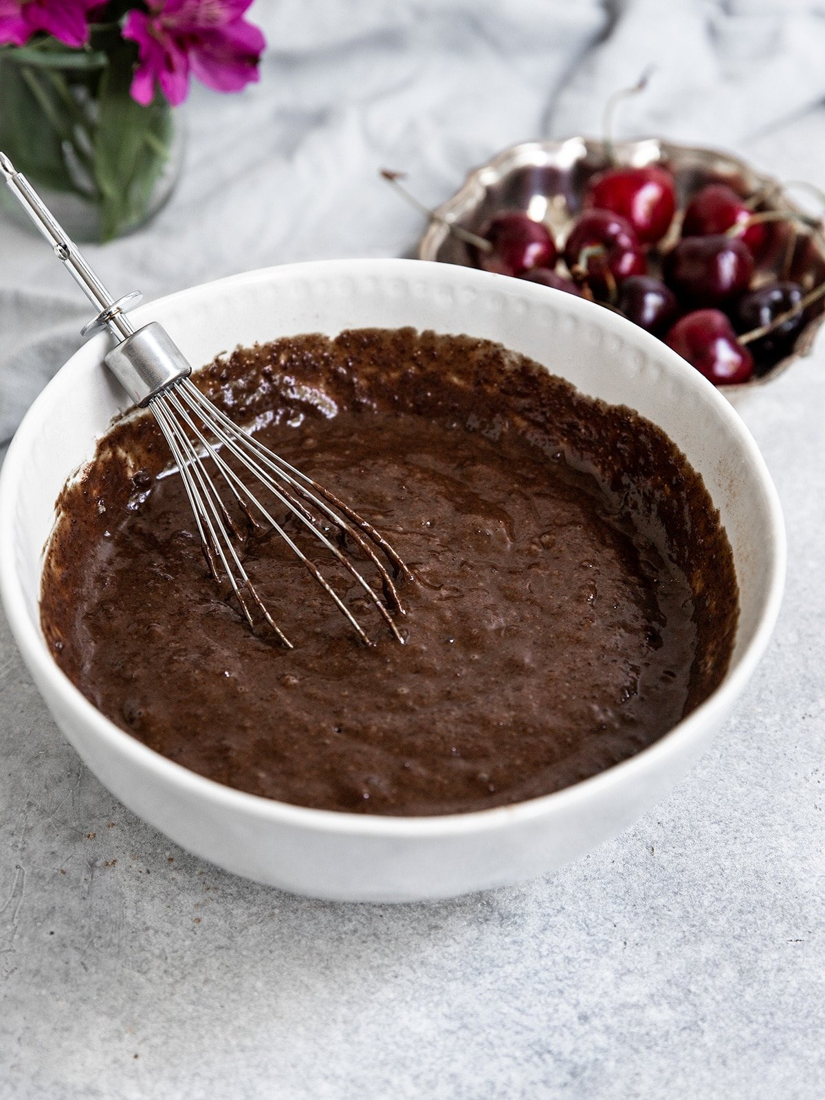 a bowl of chocolate cherry cupcake batter with a whisk