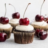 four chocolate cherry cupcakes in liners with vanilla speckled frosting and a red cherry on top of each cupcake