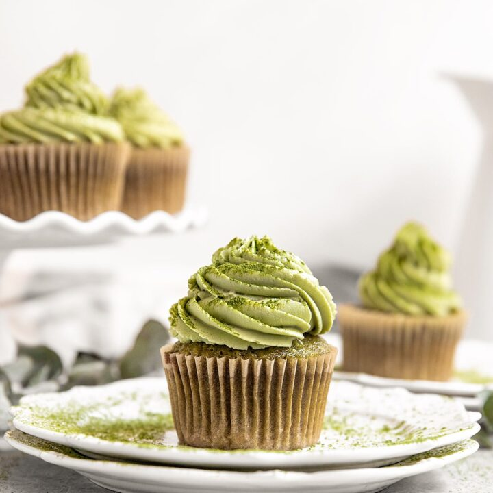 plate with a matcha green cupcake on top with matcha frosting and a dusting of matcha powder around and on top of the cupcake