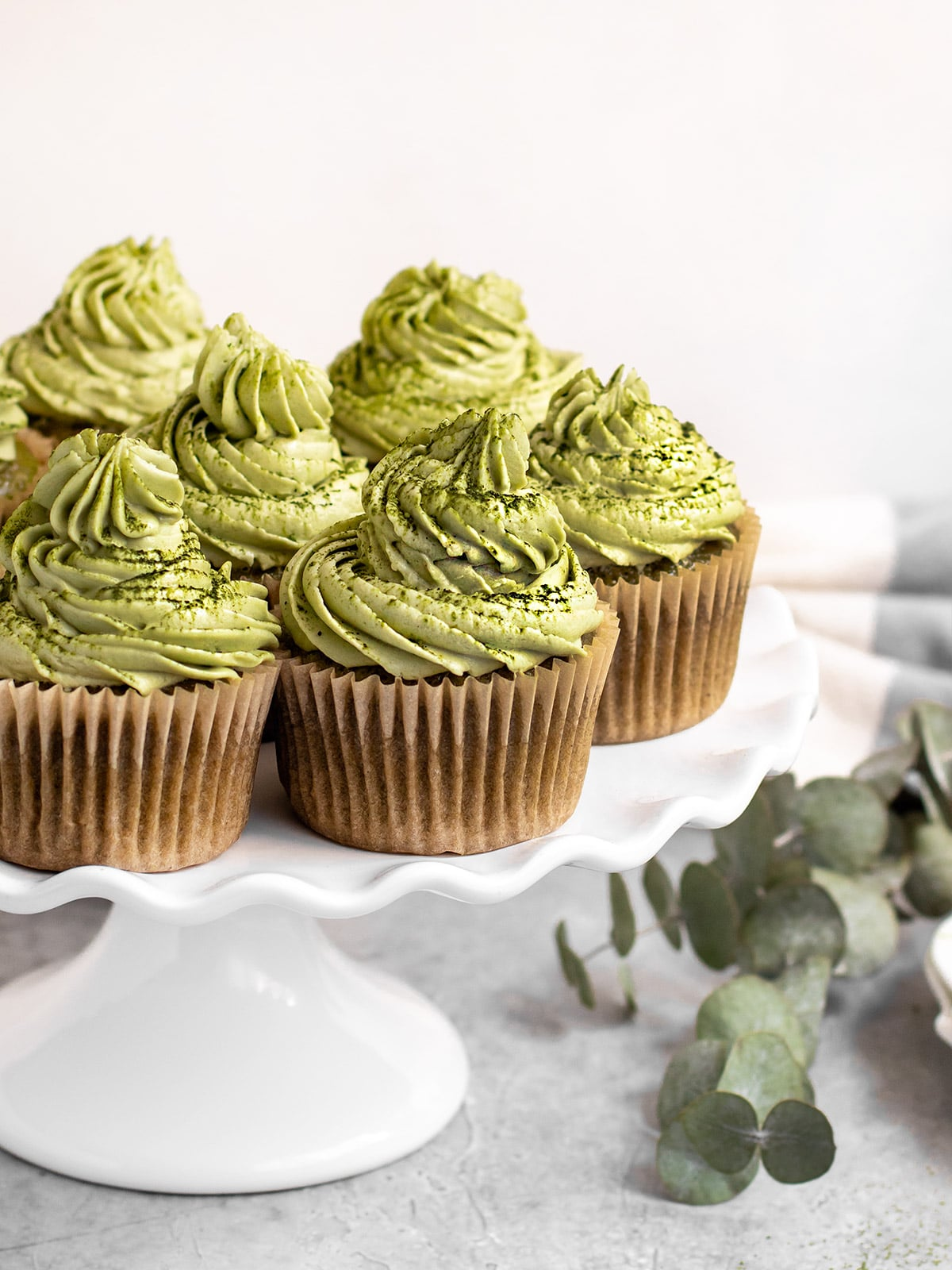 cake stand filled with matcha cupcakes with green matcha frosting on top