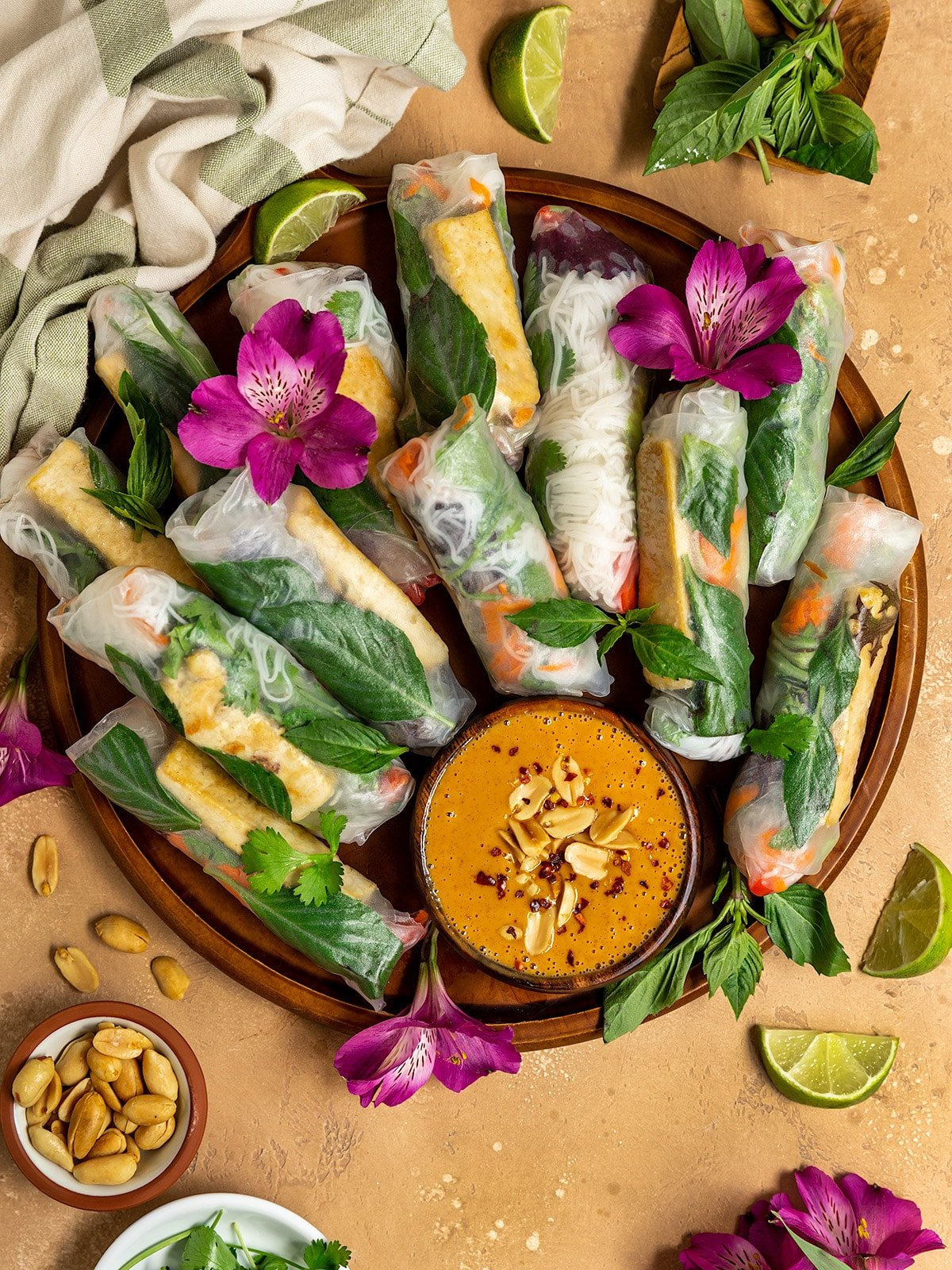 platter of fresh rolls with basil, tofu, and fresh vegetables with a side of peanut sauce, limes, peanuts, and fresh purple flowers on top