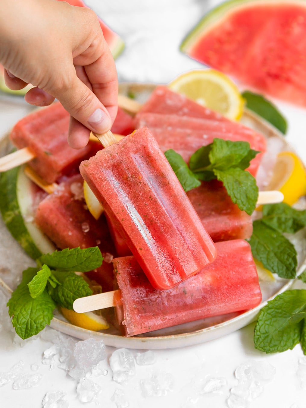 hand lifting a watermelon lemon mint popsicle from a plate filled with popsicles, fresh mint, and lemon slices