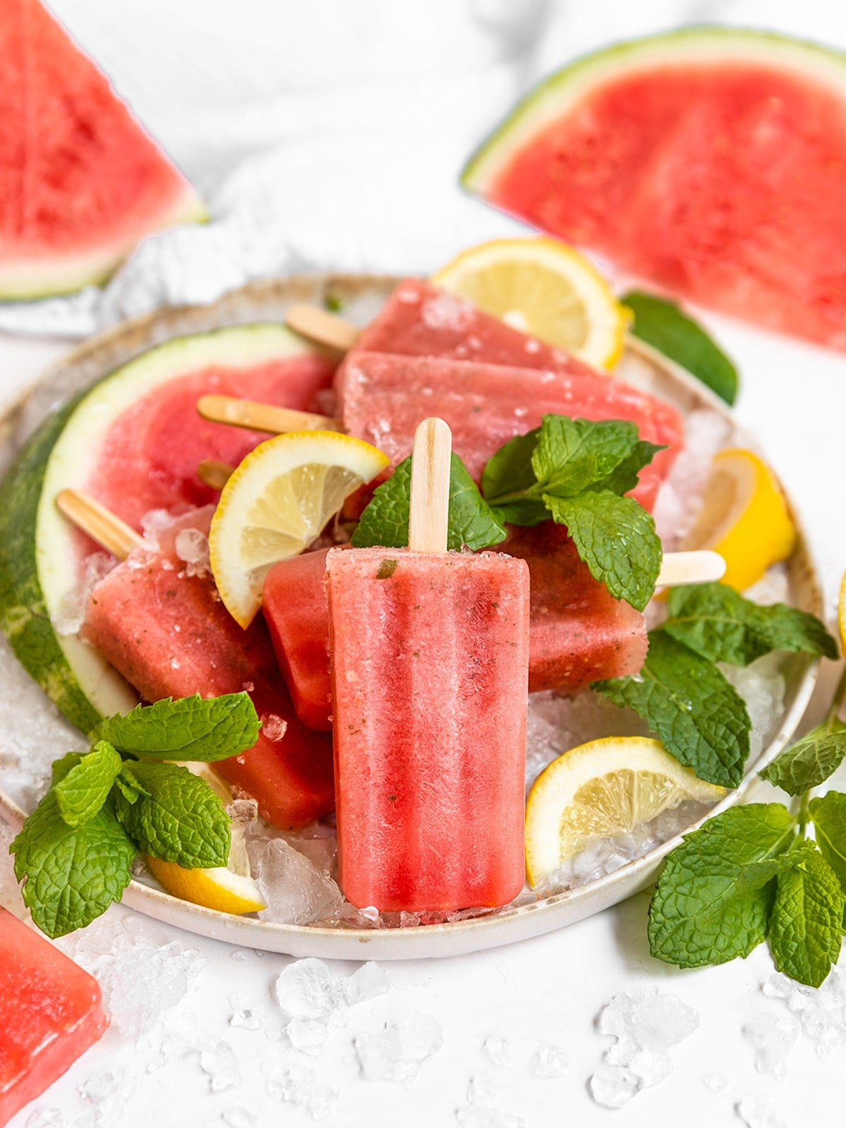 plate filled with watermelon popsicles, watermelon slices, fresh mint leaves, and lemon wedges surrounded by ice