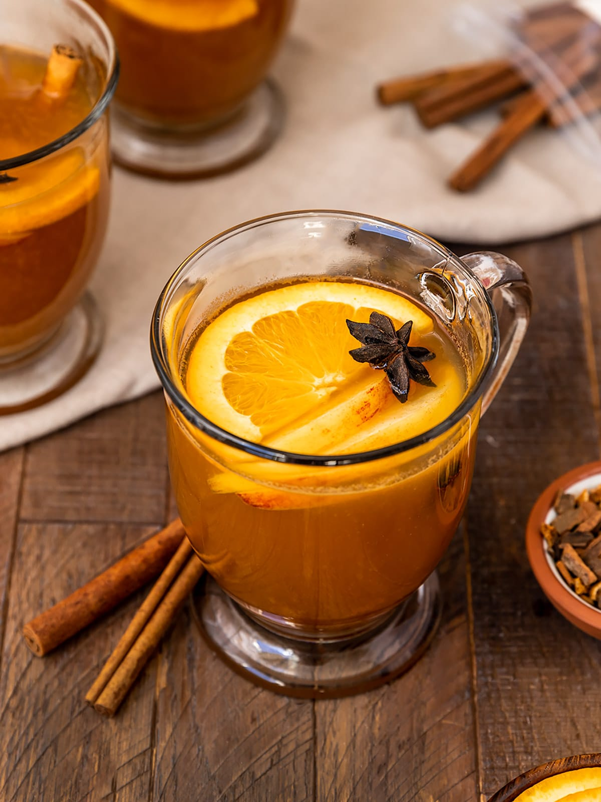 a mug of bourbon apple cider garnished with orange slices, apple slices, and star anise