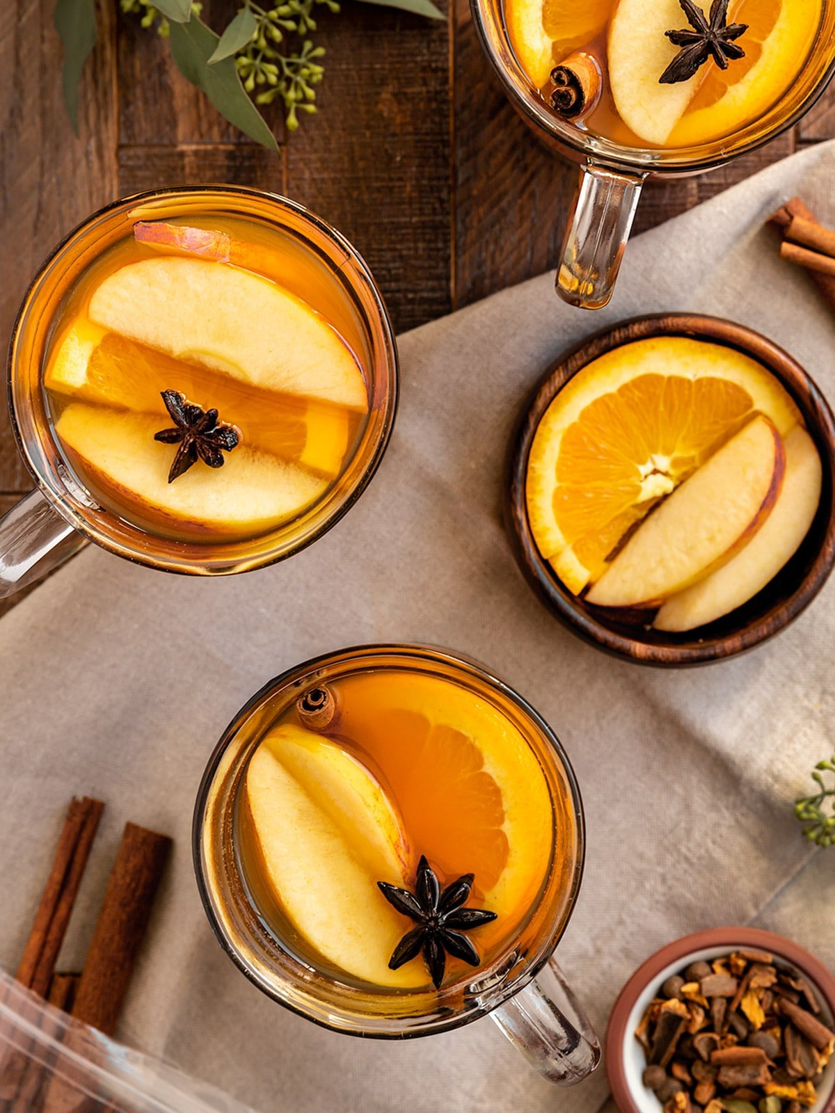 three cups of hot cider with fresh apple slices, orange slices, cinnamon sticks, and star anise as garnish
