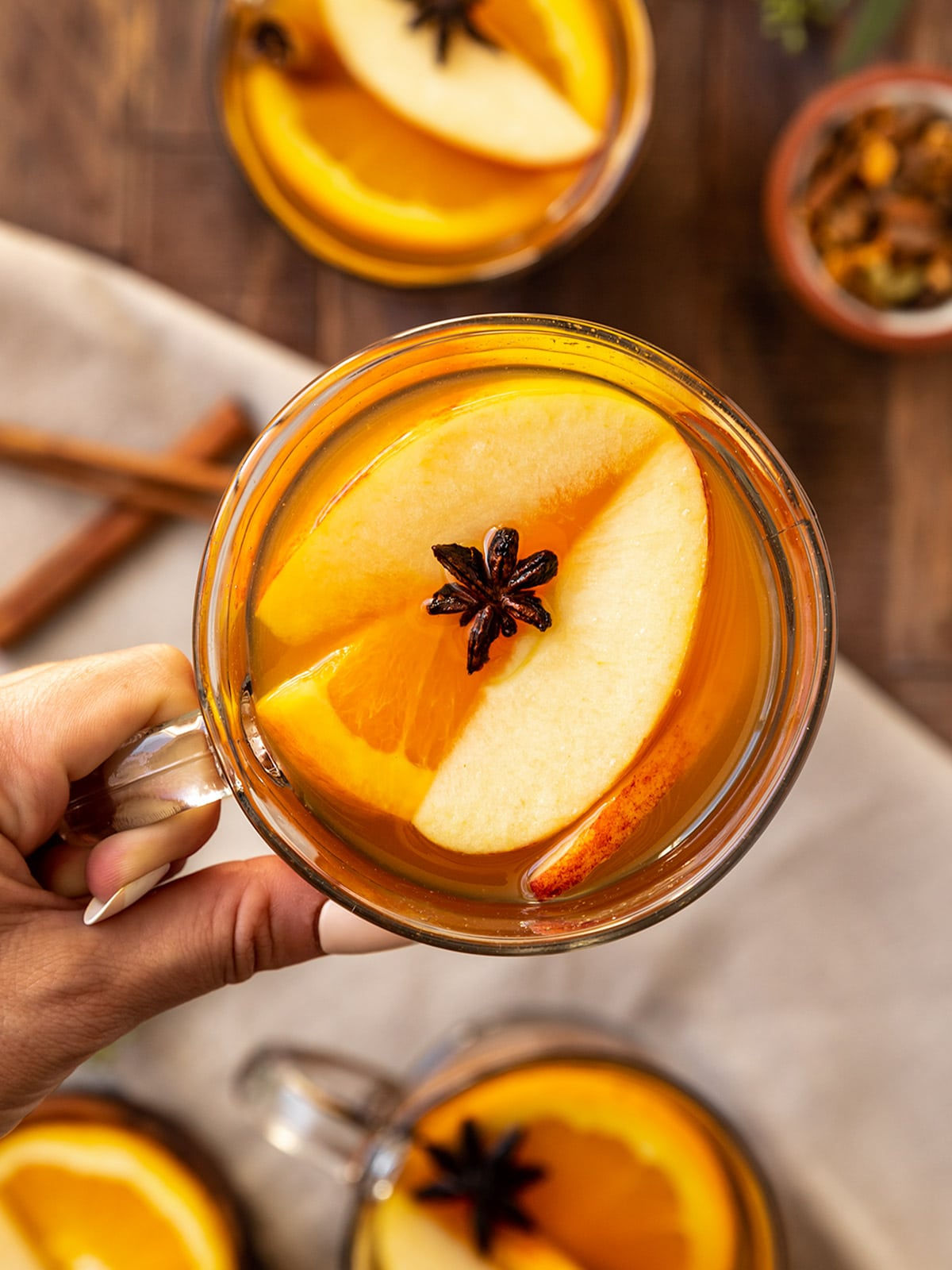 hand holding up a mug filled with hot cider garnished with apple slices, orange slices, and star anise on top