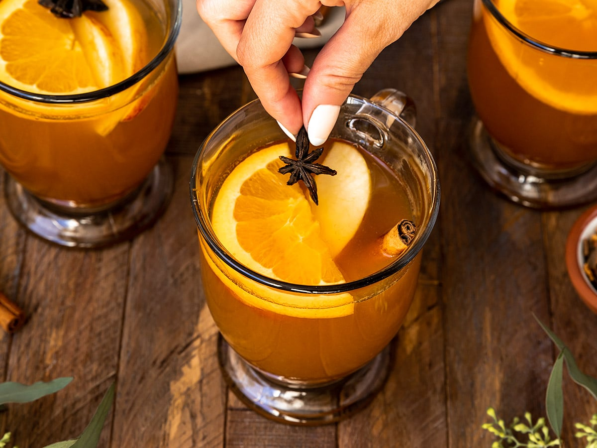 hand adding star anise to a mug filled with cider, orange slices, apple slices, and cinnamon