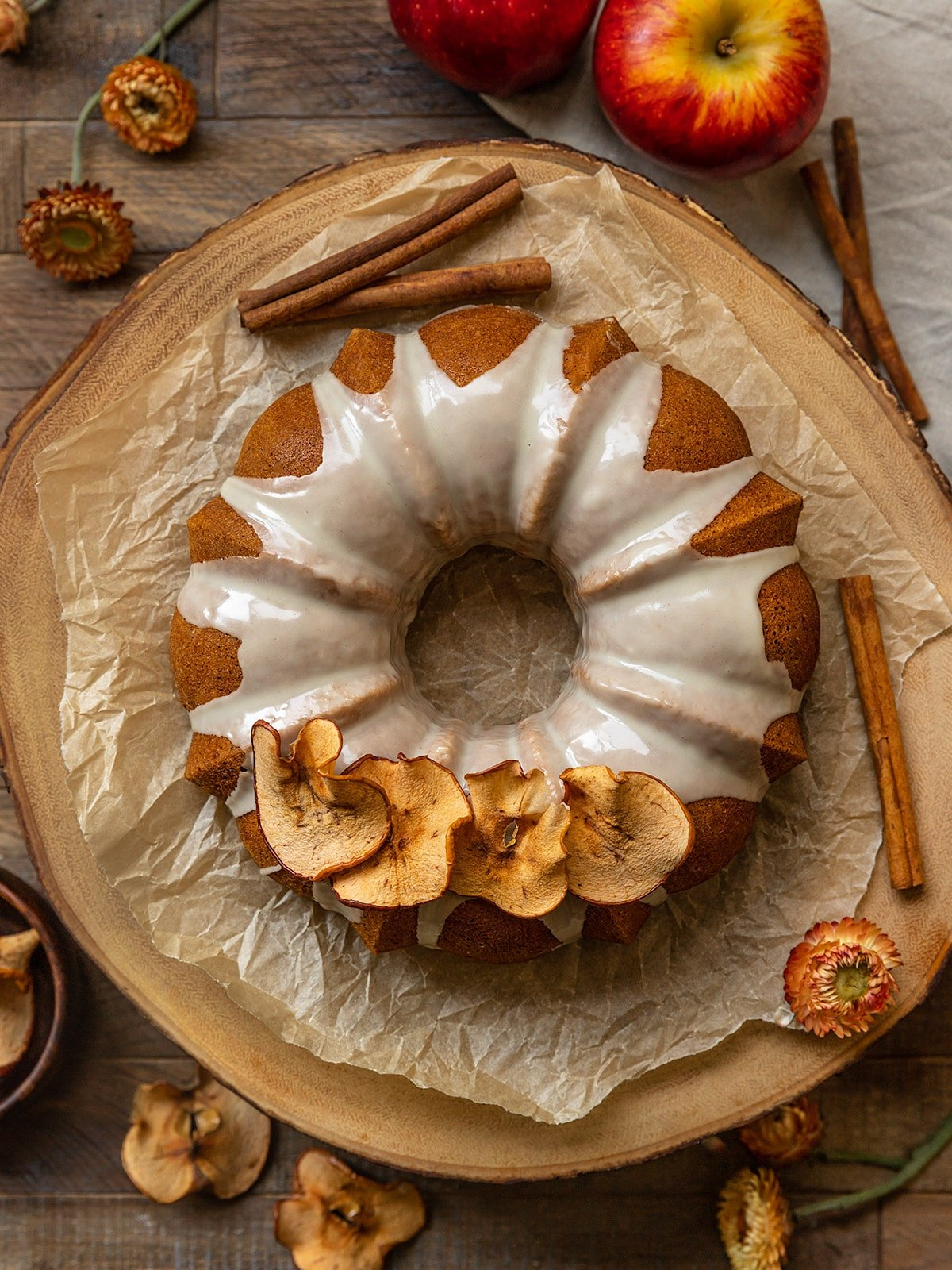 above shot of a bundt cake with glaze and dried apple slices on top on a wooden board