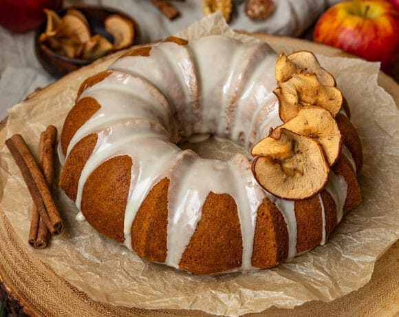 apple bundt cake with white glaze and dried apple slices on a wooden board with cinnamon sticks and apples