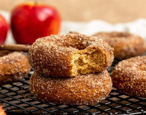 two cinnamon sugar donuts stacked on top of eachother with a bite missing from the top donut
