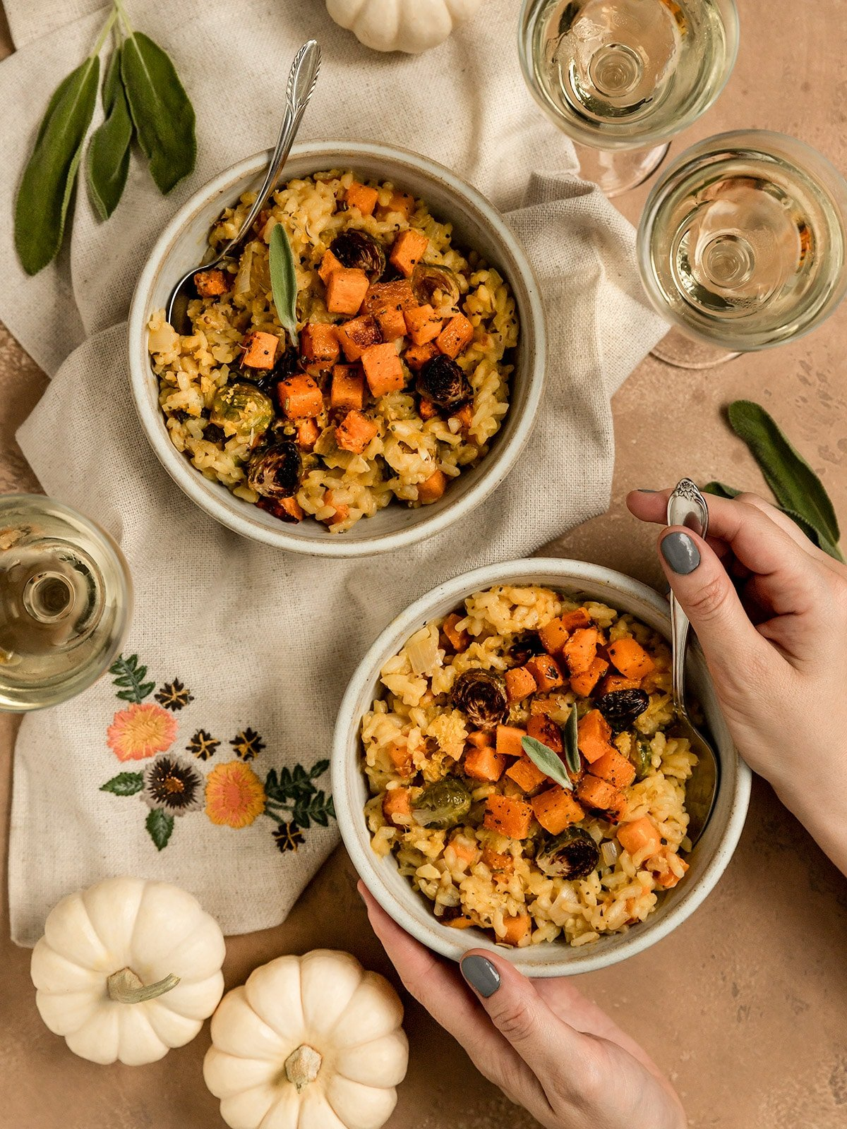 two bowls of risotto with butternut squash, brussels sprouts, and sage on top with a hand holding a spoon in one bowl