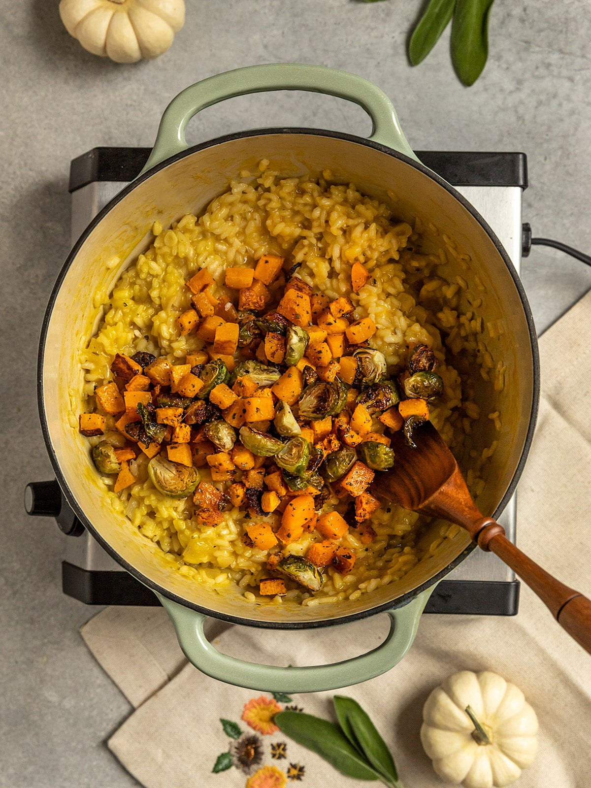 a pot of risotto rice with brussels sprouts and butternut squash added on tops
