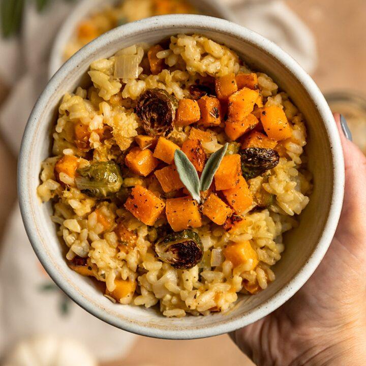 hand holding up a bowl of risotto with roasted butternut squash, brussels sprouts, and fresh sage leaves on top