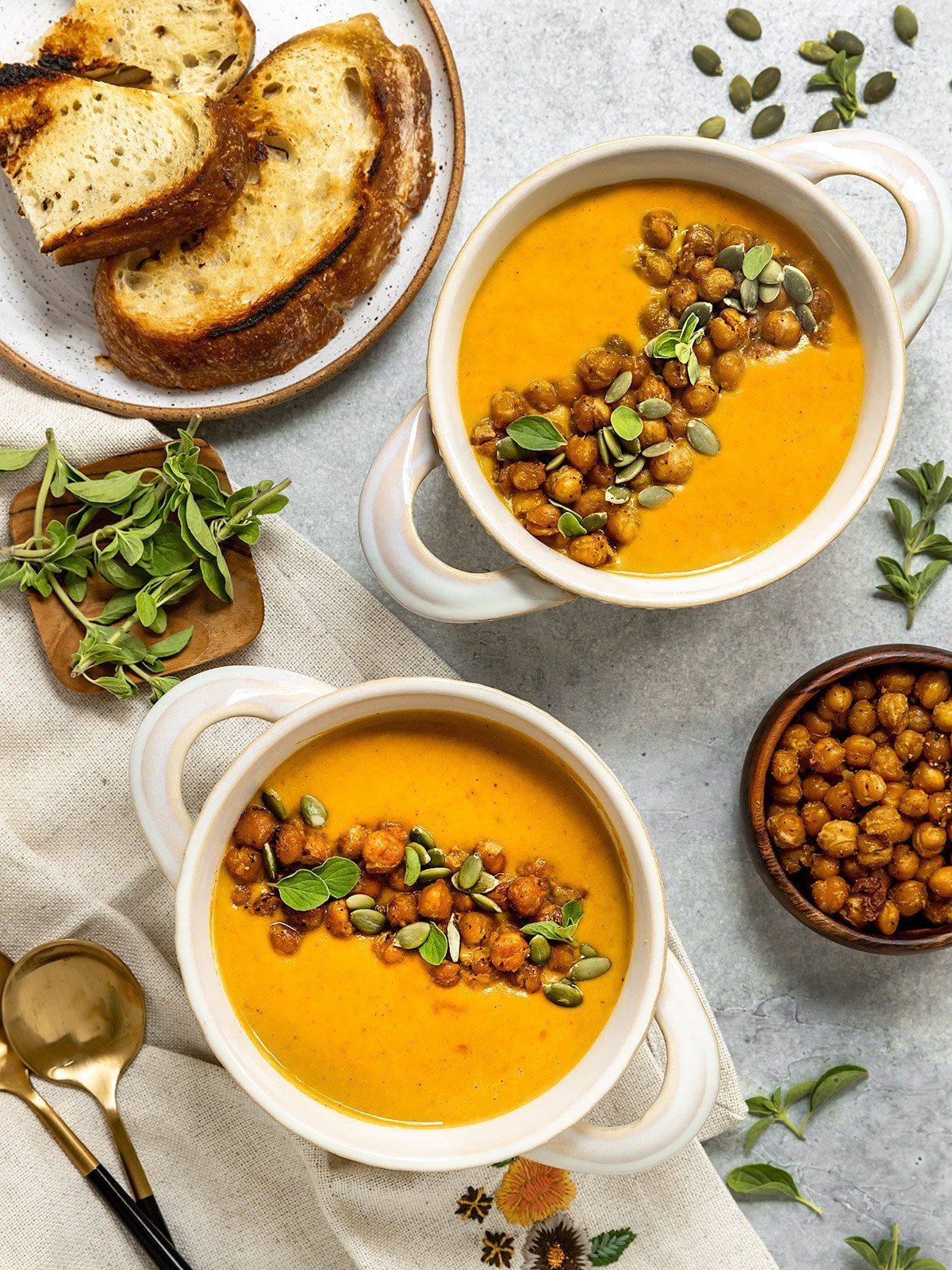 overhead shot of two bowls of soup with chickpeas, pumpkin seeds, and fresh oregano on top