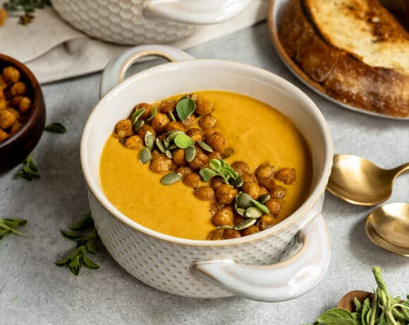 two bowls of soup with crispy chickpeas and oreganos on top with sides of extra chickpeas and toasted bread