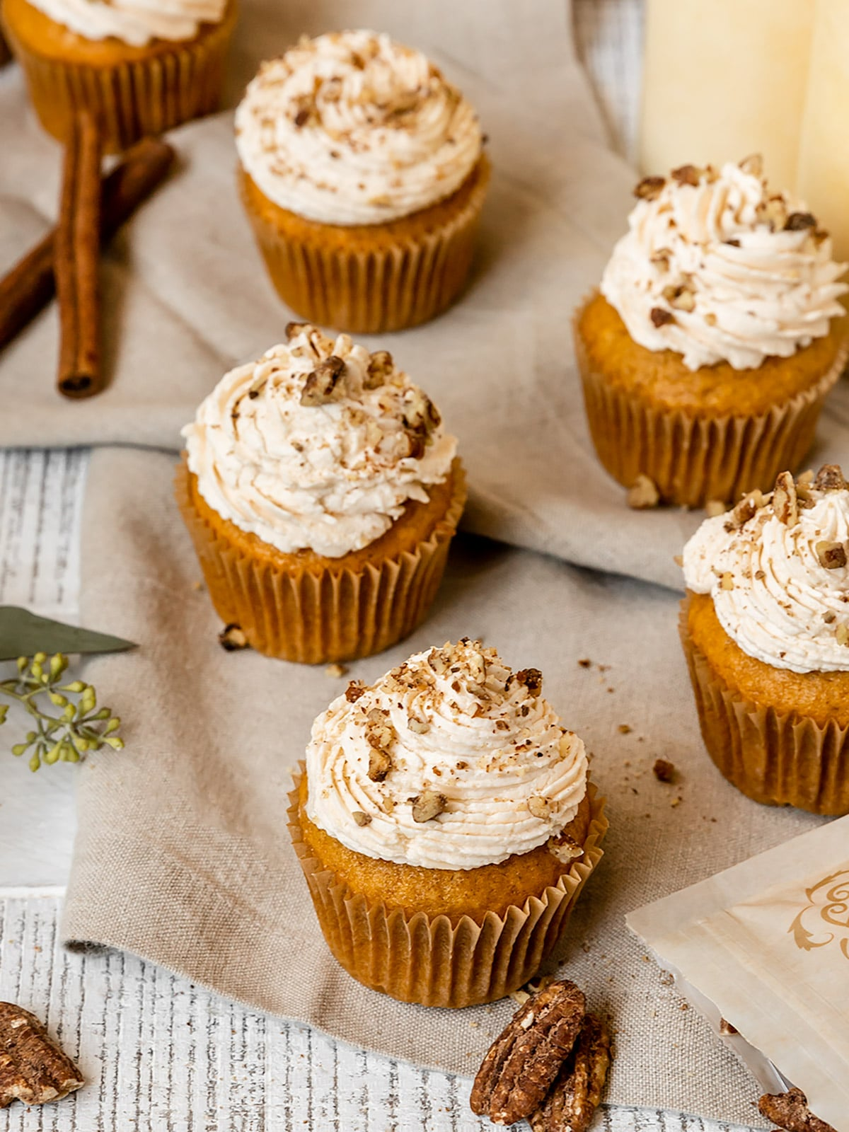 pumpkin cupcakes with frosting and pecan topping surrounded by cinnamon sticks and pecans