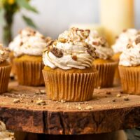 pumpkin cupcakes with maple frosting and chopped pecans on top on a large wooden cake stand