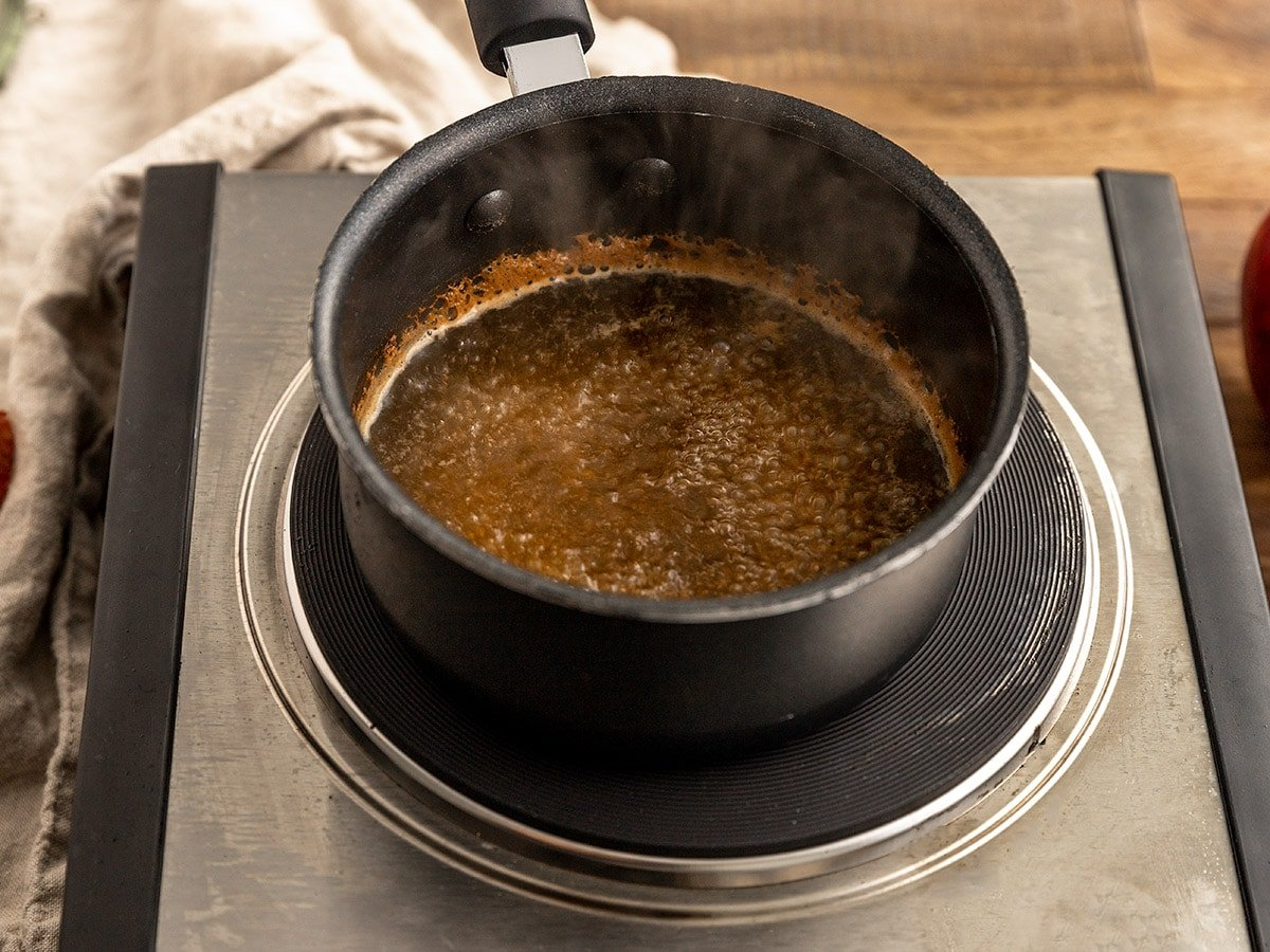a pot on a portable stove with apple cider boiling