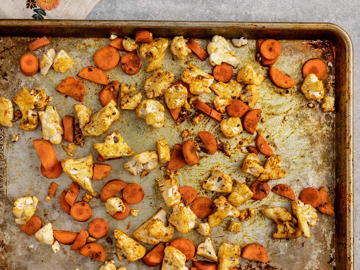 roasted chopped carrots and cauliflower on an aluminum sheet pan