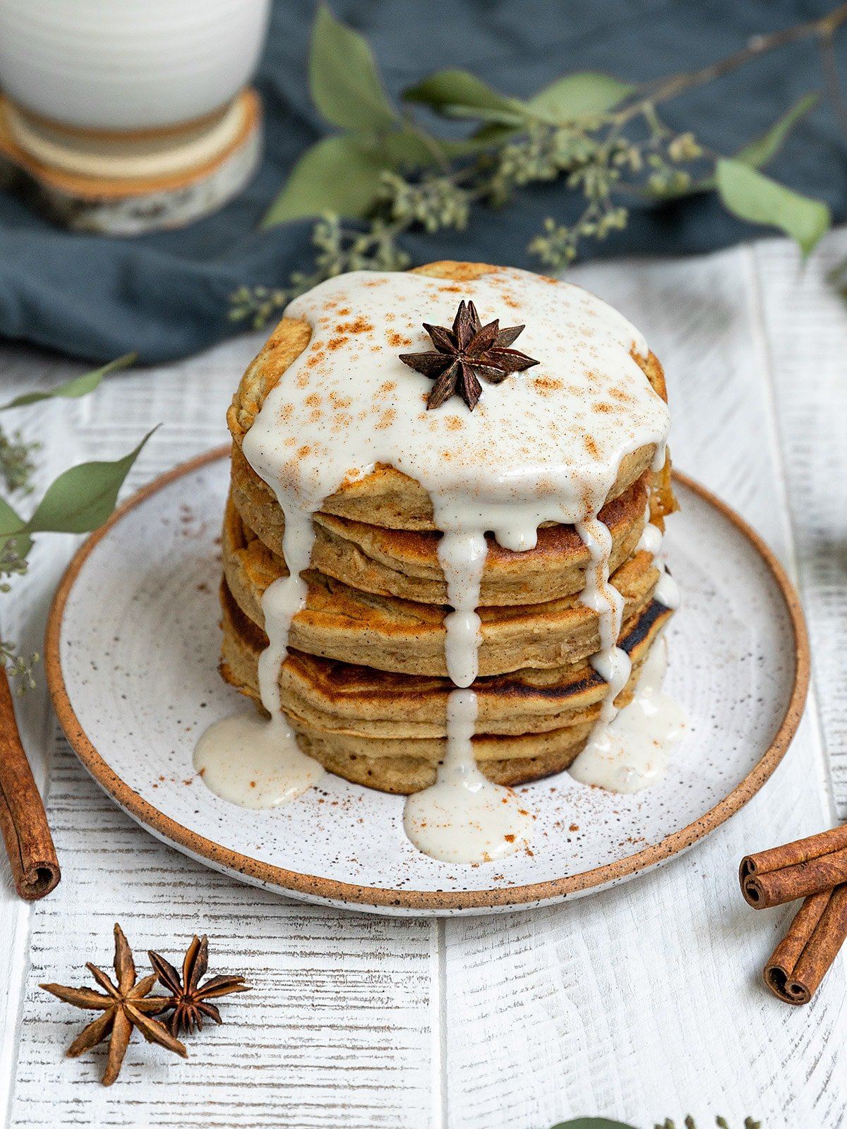 a stack of 5 pancakes on a plate topped with yogurt and whole star anise