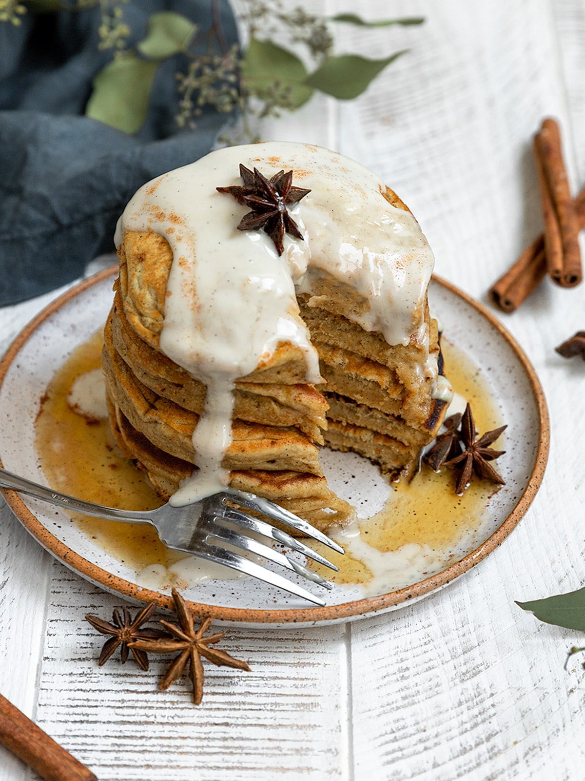 a stack of pancakes with a large slice taken out and a fork