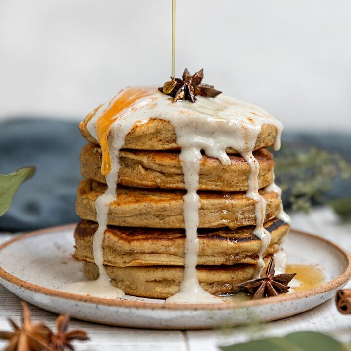 a large stack of pancakes with yogurt and star anise on top being drizzled with maple syrup