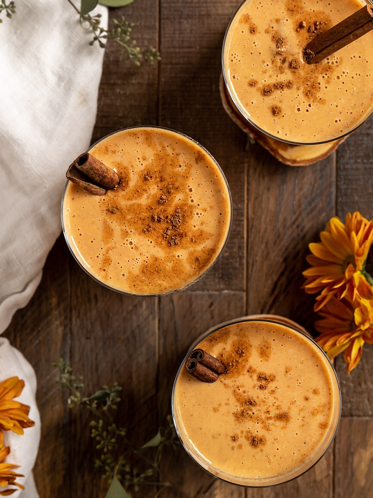 overhead shot of three smoothies with cinnamon sticks inside and pumpkin pie spice sprinkled on top