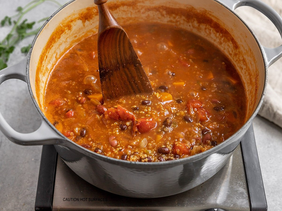 pot of chili being stirred with a wooden spoon
