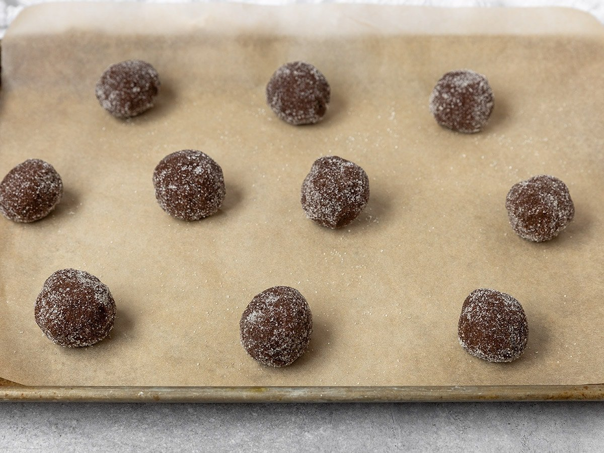 unbaked chocolate sugar cookie dough balls on parchment paper lined baking sheet