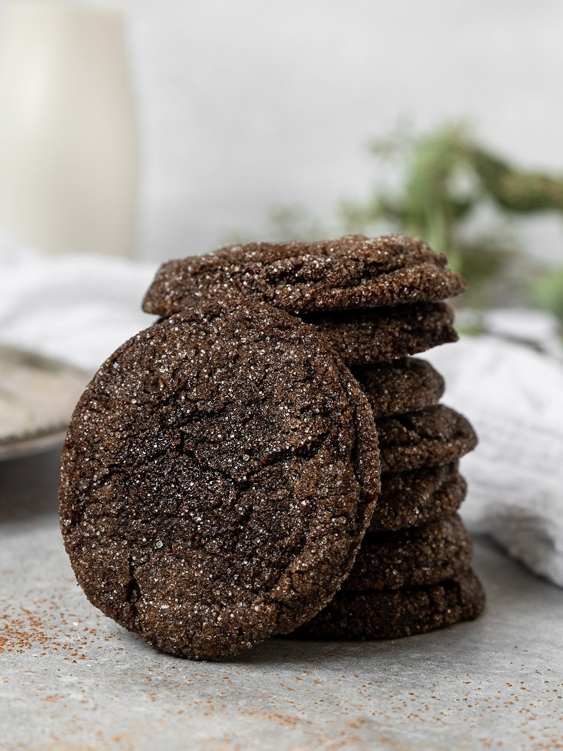chocolate sugar cookie resting against a stack of chocolate cookies