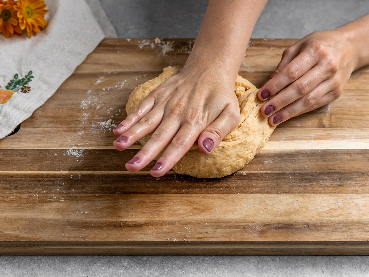 hand kneading dough on a wooden board