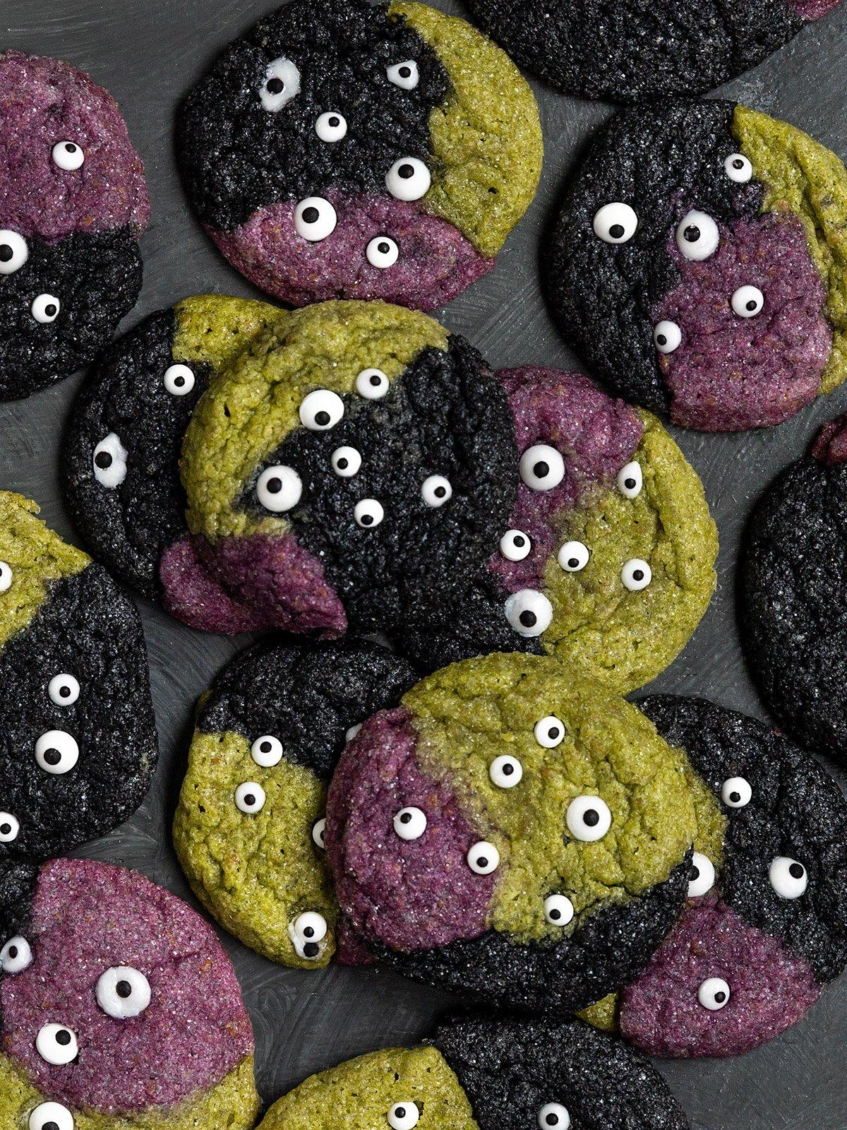 overhead shot of green,purple, and black cookies with sprinkle eye cookies