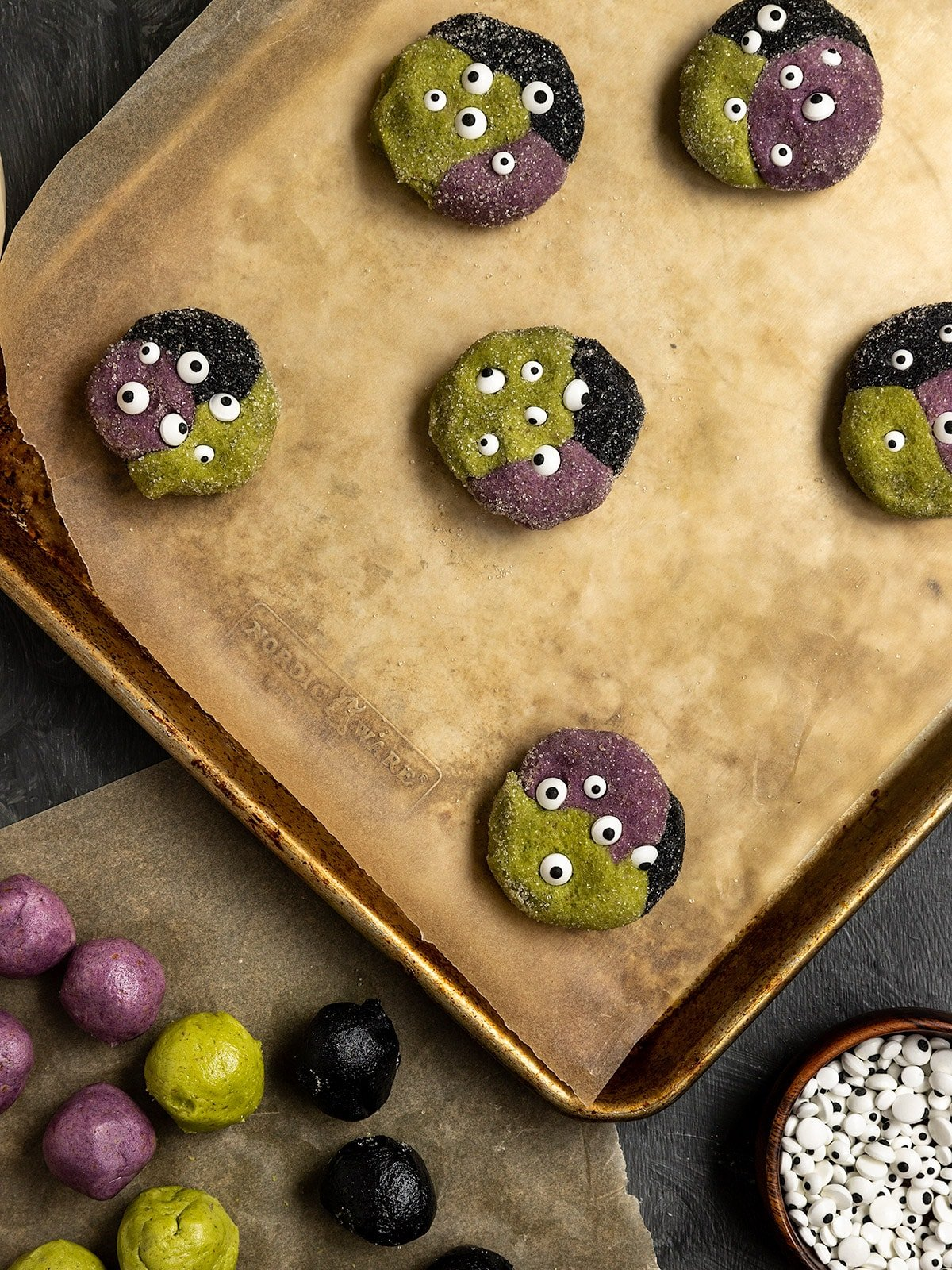 a tray of green, purple, and black cookie dough balls rolled in sugar with sprinkle eyes before baking