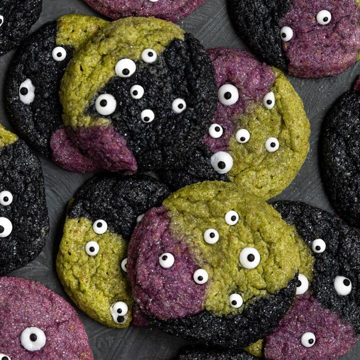overhead shot of green, purple, and black cookies with sprinkle eye cookies