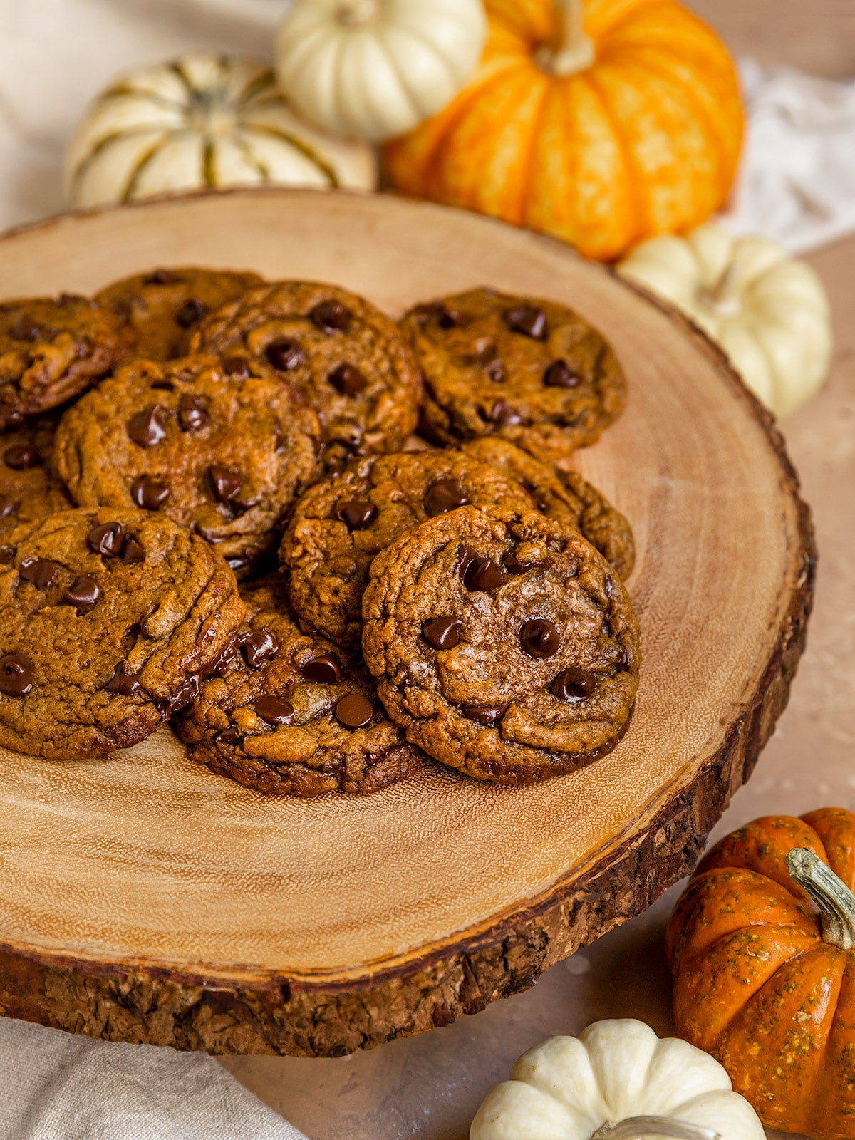 a pile of pumpkin chocolate chip cookies on a wooden board with mini pumpkinds