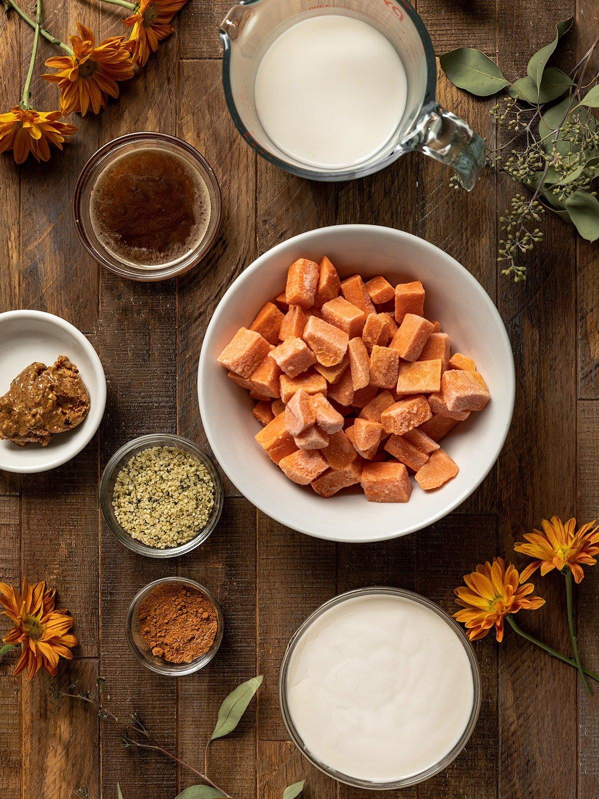 overhead shot of ingredients including frozen cubed sweet potato, maple syrup, milk, yogurt, hemp seeds, pumpkin pie spice, almond butter, and salt
