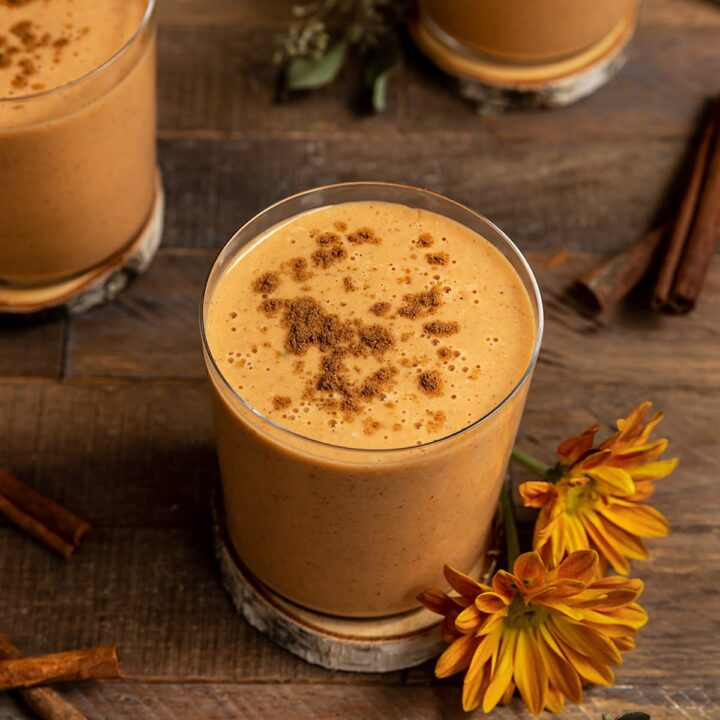 a clear glass filled with sweet potato smoothies with pumpkin pie spice sprinkled on top