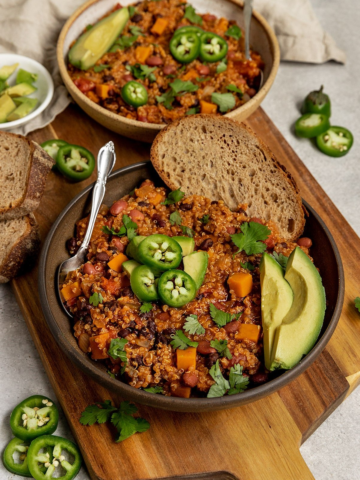 two bowls of quinoa butternut squash and bean chili with jalapeño slices, avocado slices, cilantro, and a slice of bread on top